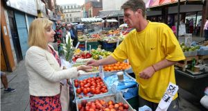Ruth O'Connor buying from Gary Adams at his fruit and veg stall on Moore Street, Dublin.  Photograph: Dara Mac Donaill