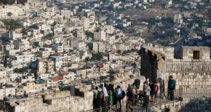 Arab neighbourhoods in east Jerusalem are seen in the background as tourists walk along  a wall surrounding Jerusalem's old city yesterday. A 10-minute drive from where negotiators will sit down today  to resume long-stalled Middle East peace talks, Israeli bulldozers are busy reshaping land that Palestinians want for their future state. Photograph: Reuters