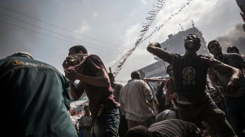 A melee of pro-Morsi supporters throwing stones.  Photograph: Narciso Contreras/The New York Times