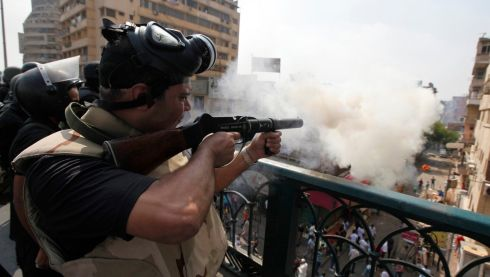 Riot police fire tear gas from a balcony. Photograph: Mohamed Abd El Ghany/Reuters