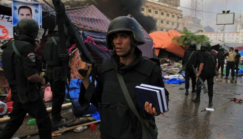 A riot police officer holds copies of the Koran as protesters are cleared from Rabaa Adawiya square. Photograph: Reuters