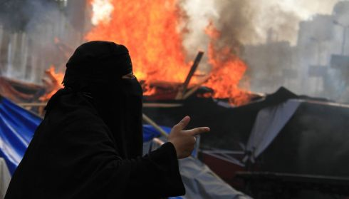 A member of the Muslim Brotherhood and supporter of Morsi shouts slogans as riot police. Photograph: Reuters