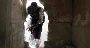 A Free Syrian Army fighter moves through a hole in a wall in the Bab al-Nasr neighborhood of Aleppo yesterday. Aleppo is one of three locations to be visited by a UN chemical weapons inspection team. Photograph: Melhem Barakat/Reuters.