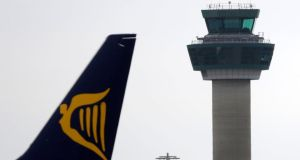 The tailfin of a Ryanair  jet passes a control tower at Stansted Airport near London. The airline has fired a pilot who questioned its safety record in a Channel 4 documentary. Photograph: Matthew Lloyd/Bloomberg.
