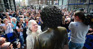 Philomena Lynott looks up at the  statue of her son after it was restored to its place on Dublin's Harry Street. Photograph: Bryan O'Brien/The Irish Times