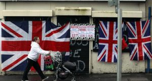 "A woman walks past a union flag attached to a shuttered shopfront on the Shankill Road in west Belfast last  December following violent protests over restrictions on flying the flag from Belfast City Hall. ""If anyone is in any doubt about how conflict disrupts business, just ask Belfast's hard-pressed merchants."" Photograph: Reuters"