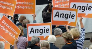 Supporters of German chancellor Angela Merkel hold up signs with her nickname during an election campaign rally  in Luebeck yesterday. Photograph: Reuters