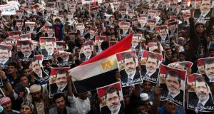 Supporters of deposed Egyptian president Mohamed Morsi hold up his photo during a march to show solidarity with his supporters in Egypt, in Sana'a, Yemen, yesterday. Photograph: Reuters
