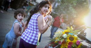 Children pass by a florist shop while walking along a street in the Imbaba neighbourhood in Cairo. Photograph:  Tara Todras-Whitehill/The New York Times.