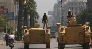 A soldier holds his weapon as he stands on an armoured personnel carrier positioned outside the state-run television station in Cairo today. Photograph:  Louafi Larbi/Reuters.