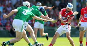 Limerick's Tom Condon and Richie McCarthy tackle Cork's Luke O'Farrell during the Munster final at the Gaelic Grounds.  Photograph: Lorraine O'Sullivan/Inpho