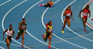 Allyson Felix of the US (top) on the ground after injuring her hamstring in the 200m final, as Shelly-Ann Fraser-Pryce of Jamaica (bottom centre) sprints to victory. Photograph: Denis Balibouse/Reuters