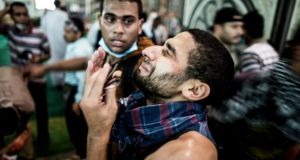 A pro-Morsi demonstrator at Al-Nour mosque on Ramses Square in Cairo reacts as a friend who was wounded after security forces opened fire on protesters is treated. Photograph: Bryan Denton/The New York Times