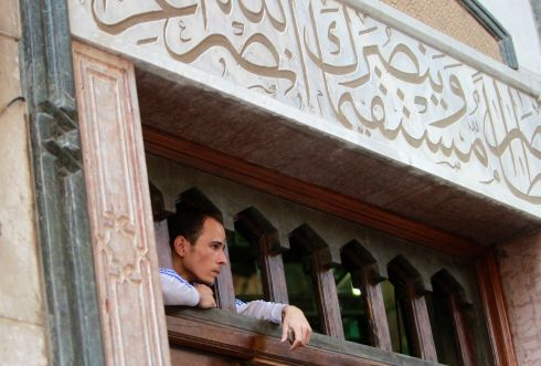 A protester who supports ousted Egyptian president Mohamed Morsi looks through an opening at the top of an entrance to the al-Fath mosque. Photograph: Mohamed Abd El Ghany/Reuters