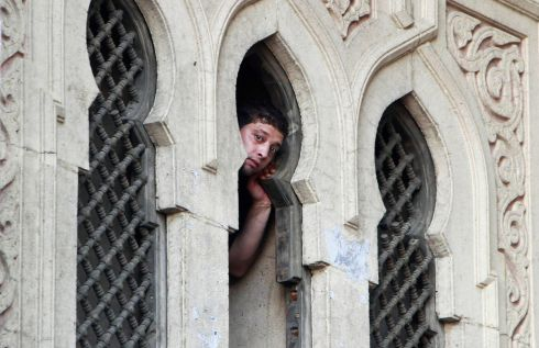 A protester looks through a window. Photograph: Mohamed Abd El Ghany/Reuters