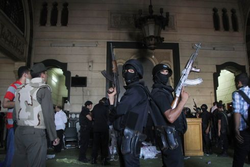 Policemen stand guard inside a room of the al-Fath mosque. Photograph: Muhammad Hamed/Reuters