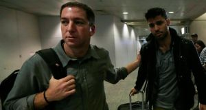 "Journalist Glenn Greenwald (left) with his partner David Miranda in Rio de Janeiro's international airport yesterday. Mr Miranda said he was questioned by six agents on his ""entire life"". Photograph: Ricardo Moraes/Reuters"