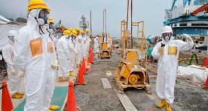 Members of a monitoring  panel inspect the construction site of the shore barrier, intended to stop radioactive water from leaking into the sea, near reactor buildings at the Fukushima Daiichi nuclear power plant. Photograph: Reuters/Kyodo