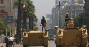 A soldier holds his weapon as he stands on an armoured personnel carrier positioned outside the state-run television station in Cairo. The military shut down all the Egyptian television networks that supported president Mohamed Morsi on the night he was ousted from office. Photograph: Louafi Larbi/Reuters