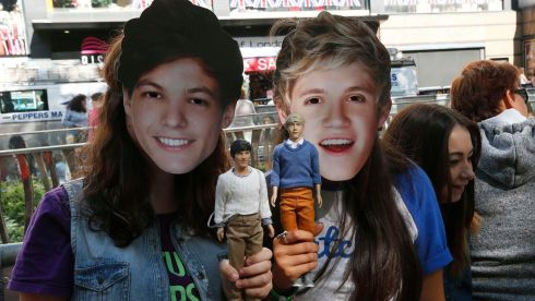 Fans pose wearing masks and holding dolls depicting One Direction band members Louis Tomlinson and Niall Horan, as they wait for the screening of the film One Direction: This is Us. REUTERS/Suzanne Plunkett