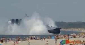 Holidaymakers enjoying the sun were startled yesterday when the world's largest hovercraft landed in their midst. The vessel was participating in military maneuvers.