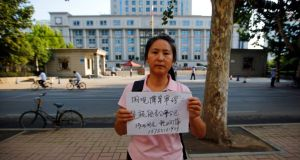"A woman holds a sign – which reads ""Watching the trial of Bo Xilai to see if fairness and justice are done"" – in front of the Jinan Intermediate People's Court building, where the trial of disgraced Chinese politician Bo Xilai will be held. Photograph: Carlos Barria/Reuters"