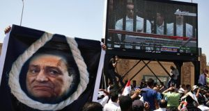Egyptians outside the police academy in Cairo watch a live video feed of the trial of former Egyptian president Hosni Mubarak and his sons in August 2011. An Egyptian court yesterday ordered Mubarak released from prison, saying all appeals by prosecutors to keep him behind bars had been exhausted. Photograph: Ed Ou/The New York Times