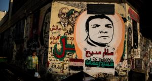 A portrait of Mohammed Badie,  left, spiritual leader of the Muslim Brotherhood, behind the face of former president Hosni Mubarak, in graffiti on the walls of Cairo's Tahrir Square, on Tuesday.  Photograph: Bryan Denton/The New York Times