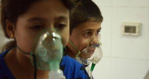 Children affected by what activists say was a gas attack breathe through oxygen masks in the Damascus suburb of Saqba. Photograph: Bassam Khabieh/Reuters