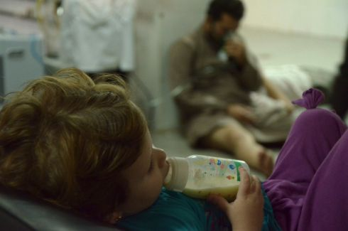 A girl feeding from a bottle, as a man affected by what activists say was a gas attack breathes through oxygen mask, at a medical center in the Damascus suburbs of Saqba. Photograph: Bassam Khabieh/Reuters