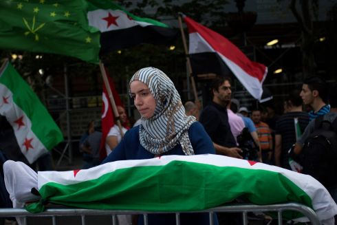 Amina, a Syrian-Canadian, holds a mock corpse covered in Syria's flag during a protest in front of the United Nations building in New York. Photograph: Adrees Latif/Reuters