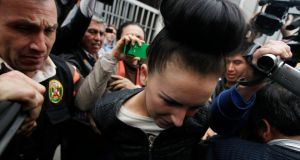 Handcuffed: Michaella McCollum Connolly with police in Peru on Tuesday. Photograph: Mariana Bazo/Reuters