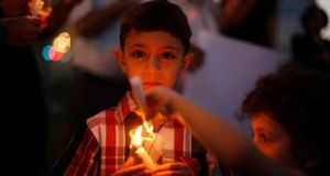 A Palestinian boy holds a candle during a vigil to show solidarity with Syrian civilians in the West Bank city of Ramallahafter hundreds were killed yesterday in rebel-held Damascus suburbs. The United Nations has demanded that Syria gives its chemical weapons experts immediate access to the suburbs where poison gas appears to have killed hundreds just a few miles from the UN team's hotel. Photograph: Mohamad Torokman/Reuters