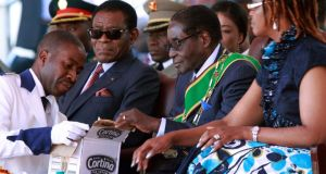Zimbabwean President Robert Mugabe, second from right, reaches for an ice cream following his inauguration in Harare yesterday. AP Photo/Tsvangirayi Mukwazhi