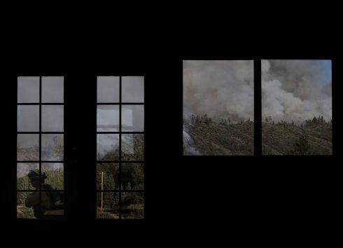 Smoke from the fire is seen through the windows of a home under construction in Groveland, California. Photograph: Justin Sullivan/Getty Images