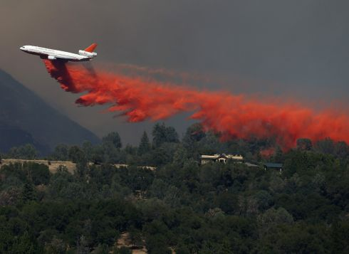 A DC-10 air tanker drops fire retardant on a ridge ahead of the advancing rim fire in Groveland, California. Photograph: Justin Sullivan/Getty Images