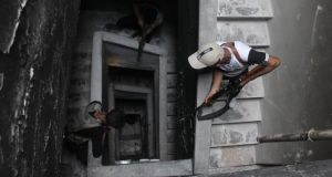Members of the Free Syrian army take cover inside a building in Aleppo's Saif al-Dawla district. Photograph: Loubna Mrie/Reuters