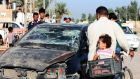 Baquba residents pass by a damaged vehicle a day after a bomb attack yesterday. Photograph: Mohammed Adnan/Reuters