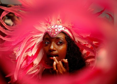Rochelle Birbal (25), a member of the Funatiks Mas Band, does her make up as she tries on her costume for this year's Notting Hill Carnival at her home in Edmonton. Photograph: Mary Turner/Getty Images