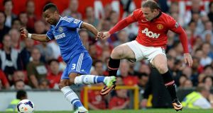 Chelsea's Ashley Cole (left) and Manchester United's Wayne Rooney battle for the ball at Old Trafford. Photograph: Martin Rickett/PA Wire