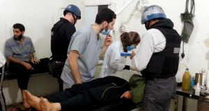UN chemical weapons experts visit victims of an apparent gas attack, at a hospital in the Damascus suburb of Mouadamiya yesterday. Photograph: Reuters