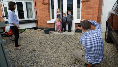 Rossa (centre) poses for a photo with his brother Cúain (6) and sisters Caoimhe (8) and Saoirse (18mts)  Sandymount, Dublin before setting off to his first day in school.  Father Barry takes the picture while mother Niamh looks on.  Photograph: Frank Miller / The Irish Times