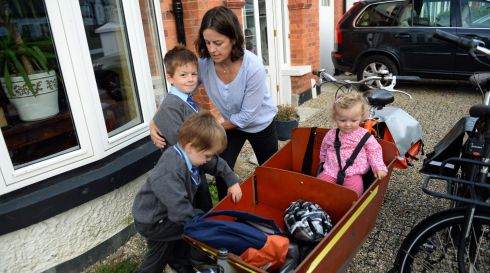 Niamh Moore gets the children into their bike carrier.  Photograph: Frank Miller / The Irish Times
