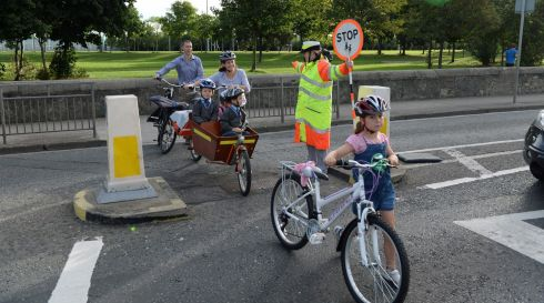 With Caoimhe (8) leading the way the family cross Strand Road with the help of the lollipop lady. Photograph: Frank Miller / The Irish Times
