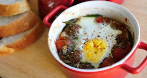 Baked eggs with spinach and tomato. Photograph: Aidan Crawley