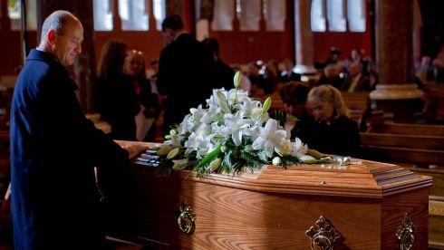 A mourners lays his hands on the coffin of Nobel Laureate poet Seamus Heaney before his funeral at the Sacred Heart Church in Donnybrook in south Dublin. Photograph: Liam McBurney/PA Wire
