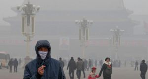 A man wears a mask on Tiananmen Square in thick haze in Beijing in January this year. Worsening air pollution has been cited as one of the reasons for declining tourist numbers. Photograph: Ng Han Guan/AP