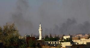 Smoke rises from al-Jazmati area after what activists said was shelling by forces loyal to Syria's President Bashar al-Assad in Aleppo yesterday. Photograph: Hamid Khatib/Reuters.