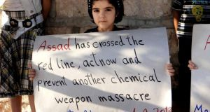 A Syrian girl holds a sign during a demonstration on Sunday in Maaret al-Numan, Idlib province, northern Syria.  Photograph: Edlib News Network ENN/AP