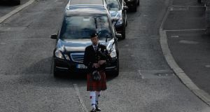 A piper leads the funeral of Seamus Heaney through Bellaghy, Co Derry, yesterday   evening. Photograph: Dara Mac Dónaill